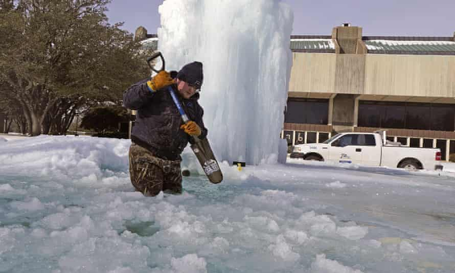 Kaleb Love, a municipal worker, breaks ice on a frozen fountain in Richardson, Texas, on Tuesday, as freezing temperatures grip the state.