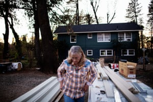 Mary Nieland in front of her 1940's farm house and in-between new hardie boy siding (fire resistant fiber cement siding) that will be used on her new studio space, Paradise, California, November 6th, 2019