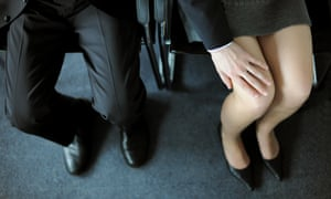 A man touches a female co-worker's leg
