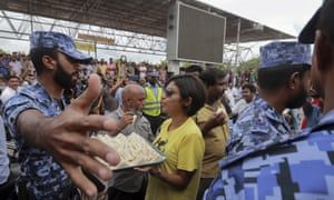 Eva Abdullah, of the Maldivian Democratic party, offers sandwiches to police personnel as they try to stop the party from holding political rallies on Friday.