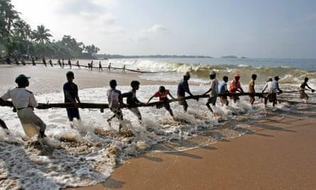 Sri Lankan fishermen pull their fishing net in on the beach in Baruwala