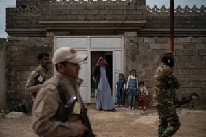 Residents watch as local militia and Iraqi army soldiers walk past their home during a raid in Badoush, Iraq, April