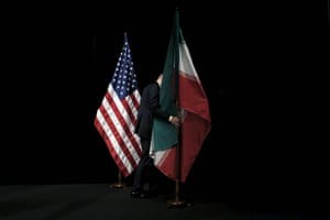 A member of staff removes the Iranian flag from the stage after the nuclear talks at in Vienna. Iran and six major world powers reached a nuclear deal this week capping more than a decade of on-off negotiations with an agreement that could potentially transform the Middle East, and which Israel called an 'historic surrender'.