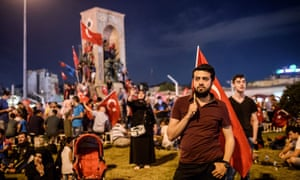 A pro-Erdogan supporter holds a Turkish national flag during a rally at Taksim square in Istanbul.