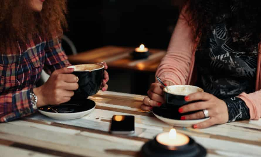 Cropped shot of two women sitting at restaurant holding cups of coffee
