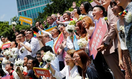 Gay and lesbian newlyweds pose for group photo at a pro same-sex marriage party after registering their marriages in Taipei.