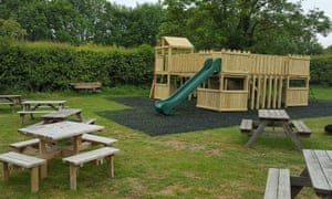 Play area and picnic benches outside the barn and gift shop at Hitchin Lavender, Hertfordshire.