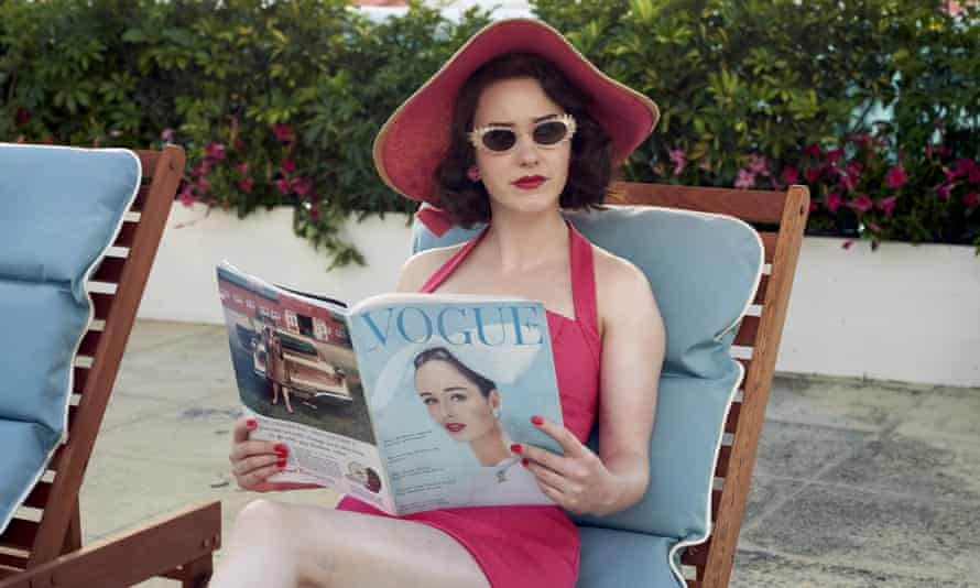 Rachel Brosnahan as Mrs Maisel, on a sunlounger in a one-piece, shades and a hat, and holding a copy of Vogue, in a scene from The Marvelous Mrs. Maisel