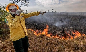 A worker of the Brazilian Institute of the Environment points at the damage caused by a fire in Manicore, Amazonas, Brazil on 26 August 2019.