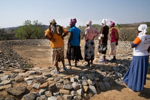 Women look at a dried out fish farm in their village, no longer providing food and income