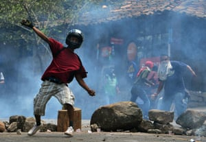 Residents throw stones at riot police during a protest against a housing project in Tegucigalpa, Honduras