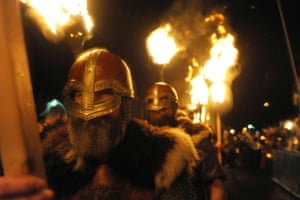 Participants dressed as Vikings carry torches