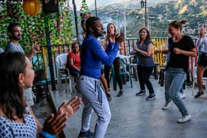 A tour guide teaches tourists how to dance to Latin American rhythms