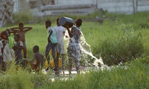 A young girl splashes water on her body at a watering point in Beira, Mozambique