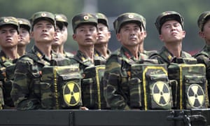 North Korean soldiers carry packs marked with the nuclear symbol during a parade in Pyongyang.