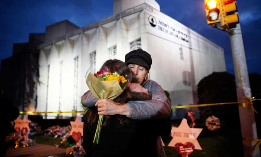Two women hug before placing flowers at the Star of David memorial in front of the synagogue.