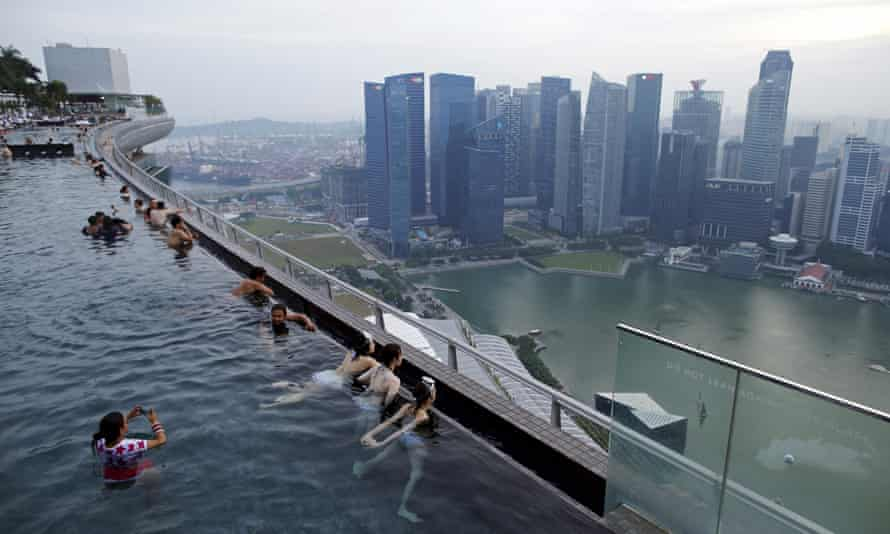 Tourists look at the skyline of Singapore city from an infinity pool at the 57-storey Marina Bay Sands hotel.