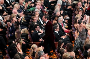 Actors Lupita Nyong'o, Armie Hammer and others head out of the theatre as part of a skit during the Oscars show