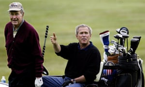 George HW Bush and George W Bush play golf together in 2003 at Kennebunkport, Maine.