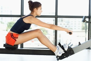 side profile of a young woman exercising on a rowing machine in a gym