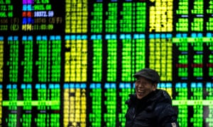 An investor at a securities company in Shanghai on Friday. On China's trading exchanges, green represents stocks in negative territory.