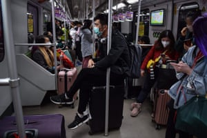 A man wearing a protective mask sits on luggage as he travels on the subway in Shanghai on January 22, 2020