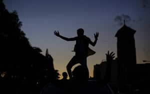 A reveller dances on the roof of a vehicle as he and others celebrate outside the parliament building in Harare