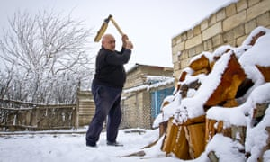 Man chops wood in the snow