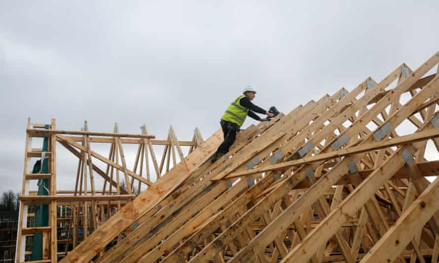 'The shortage of construction skills is the worst recorded.' A builder climbs across roof timbers at a Persimmon construction site in Cranfield.