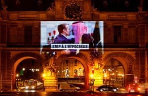 Paris, France. A projection on the Louvre museum by Amnesty International depicts President Emmanuel Macron greeting Mohammed bin Salman, the Saudi crown prince, before the virtual G20 summit