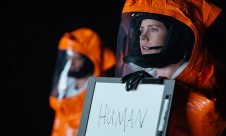 Woman in orange protective suit holds up sign saying