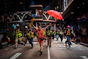 "A woman holds up an umbrella and a licence plate reading ""Love"" during violent clashes between riot police and demonstrators in the Causeway Bay district"