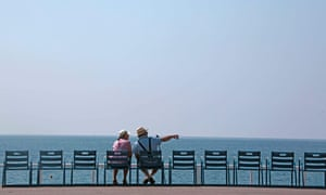 Two elderly people sit on the blue chairs of the Promenade Des Anglais near the Mediterranean Sea during a warm and sunny day in Nice, southeastern France, June 3, 2015. REUTERS/Eric Gaillard TPX IMAGES OF THE DAY