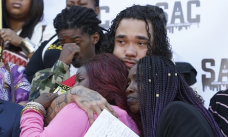Trayvon Wiseman, center, a cousin of Stephon Clark, hugs Clark's mother, SeQuette Clark, left, and grandmother, Sequitta Thompson, right, during a news conference in Sacramento.