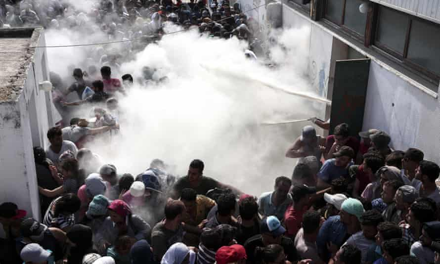 Police try to disperse hundreds of migrants by spraying them with fire extinguishers.