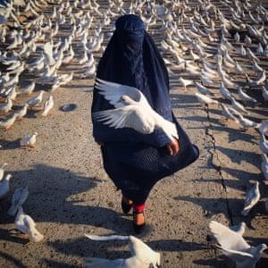 Woman with blue borghe walking through birds.