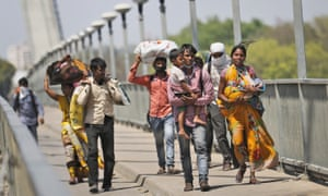 On the outskirts of Allahabad in Uttar Pradesh, Nidhi Patel and her husband, Vikas Patel, centre right, both migrant workers, carry their children as they walk home to their village.