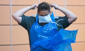 A London Ambulance worker puts on a protective mask
