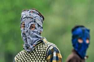 Wearing a mask made of clothing with eye holes cut out, a boy plays cricket in Srinagar, in Jammu and Kashmir