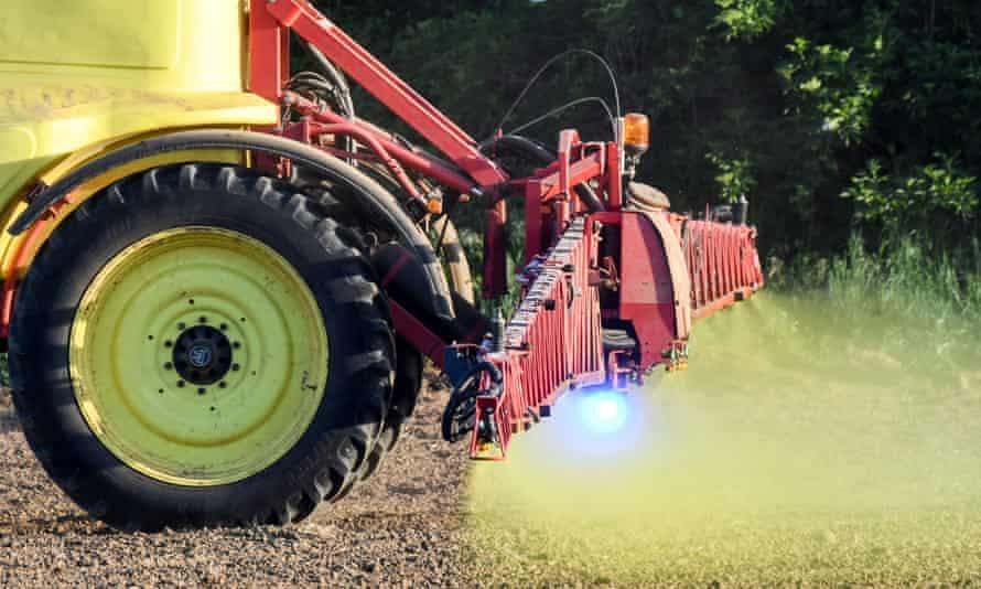 A farmer uses a herbicide