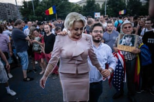 A demonstrator holds a cardboard cut-out of Viorica Dăncilă in front of her office building in Bucharest, Romania.