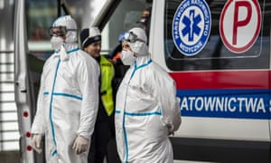 Health workers wear protective clothing as they stand to screen passengers' temperatures at the German-Polish border.