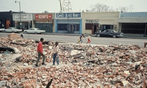 Children playing in rubble left in the wake of the Watts riots, Los Angeles, July 1966.