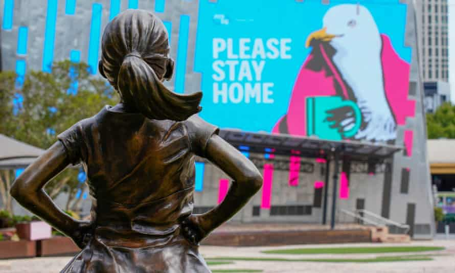 """Fearless Girl statue looks at a """"Please Stay Home"""" sign in Federation Square on the first day of a five-day COVID-19 lockdown in Melbourne"""