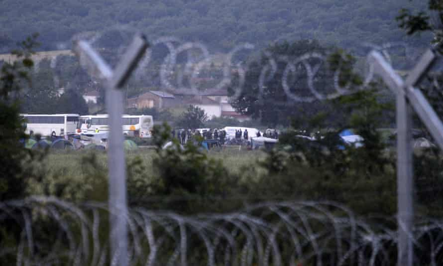 Police and buses seen through the wire fence on the perimeter of the Idomeni camp