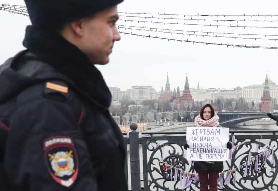 A protester holds a placard with a message reading 'Domestic violence victims need therapy not prison' on Patriarshy Bridge in Moscow.