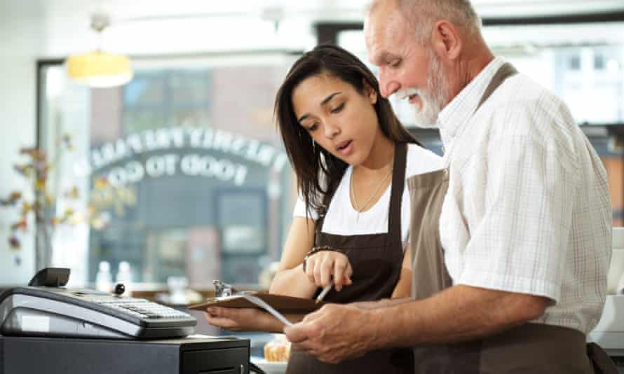 A young woman and older man working in a cafe