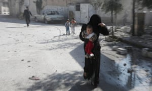 A woman and her children run for cover from Assad air strikes on Damascus.