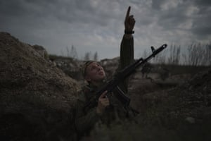 A Ukrainian soldier points at a passing helicopter as he stands in a trench on the line of separation from pro-Russian rebels near Donetsk.