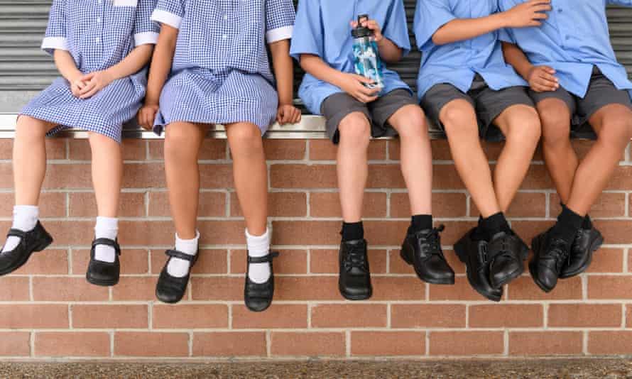 School children sitting on brick wall